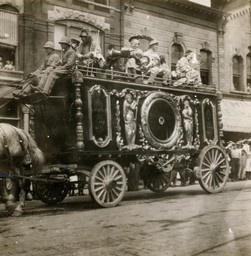A Ringling Circus wagon, pulled by a horse, with clowns riding on top, is part of a parade along a city street.