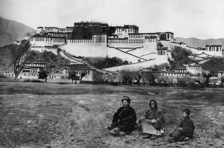 Alexandra in, dressed as a beggar and face covered in grease, Lama Yongden and a young Tibetan pose upon the backdrop of the Potala Palace, in Lhasa, Tibet's capital, in 1924. © Archives Fondation Alexandra David-Néel — Ville de Digne-les-Bains