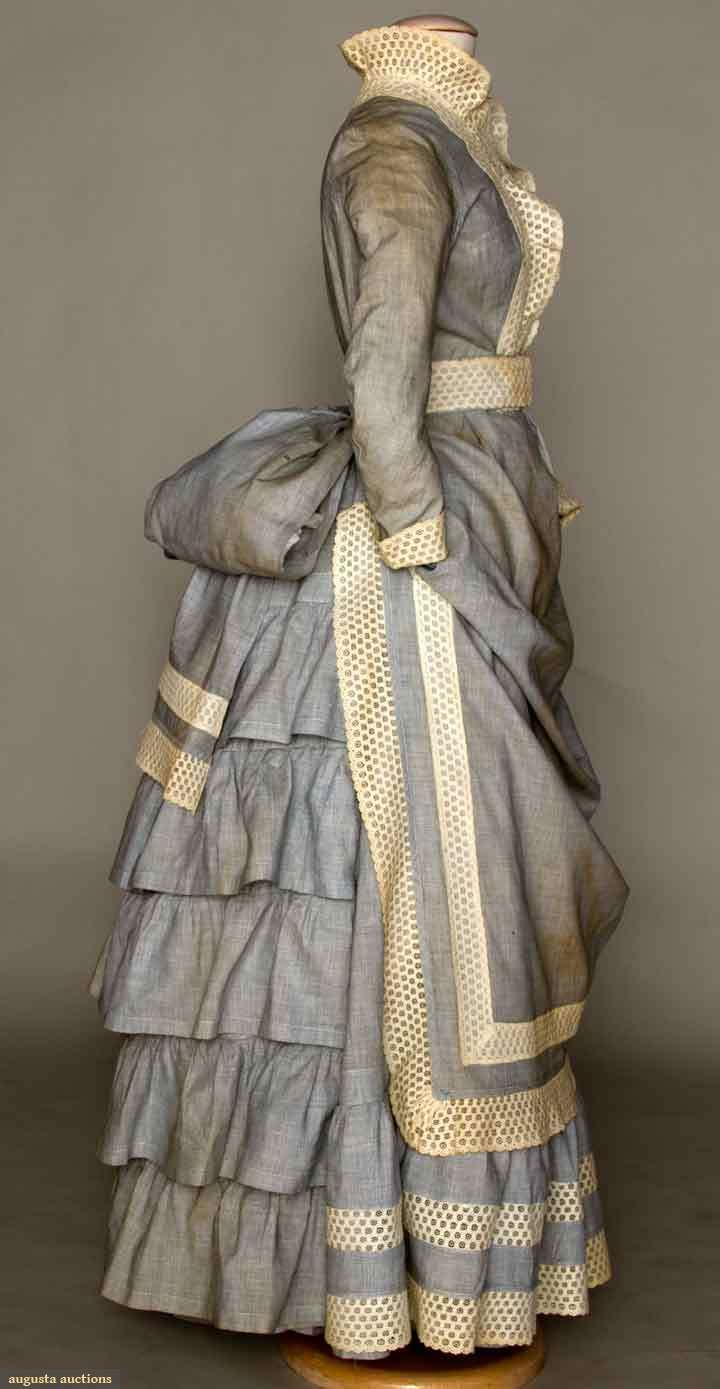 """YOUNG LADY'S SEA SIDE ENSEMBLE, c. 1880 3-piece, skirt, bodice & belt, all in blue chambray trimmed w/ ivory eyelet bands: skirt w/ apron front, hem ruffle & 5 ruffles over bustle back; fitted blouse, front thread woven buttons, band collar; eyelet belt w/ huge chambray back bow, B 30"""", W 20"""", Skirt L 52"""", (couple tiny holes, brown discoloration on chambray) very good; t/w 1 red & white striped cotton shirt waist, excellent. Brooklyn Museum"""