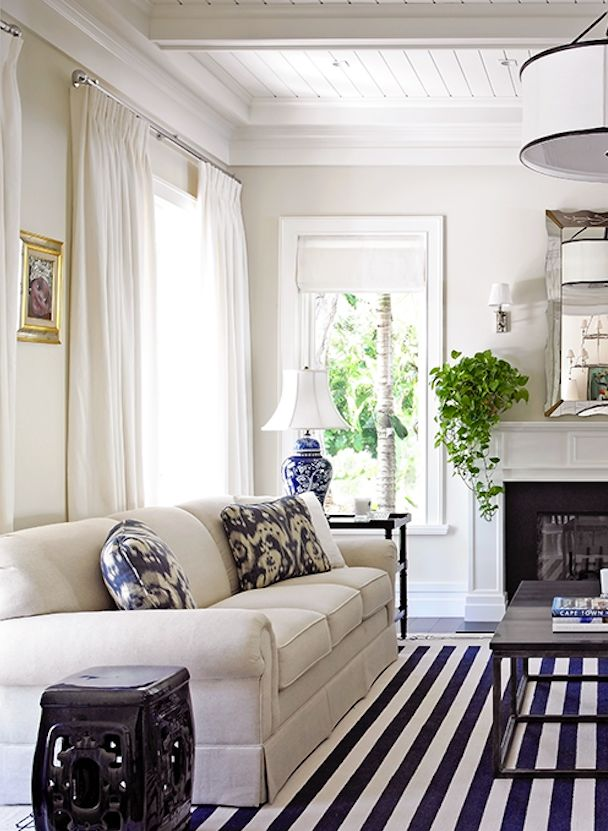 Modern coastal living room with a versatile white sofa, blue patterned accent pillows and a navy and white striped rug.