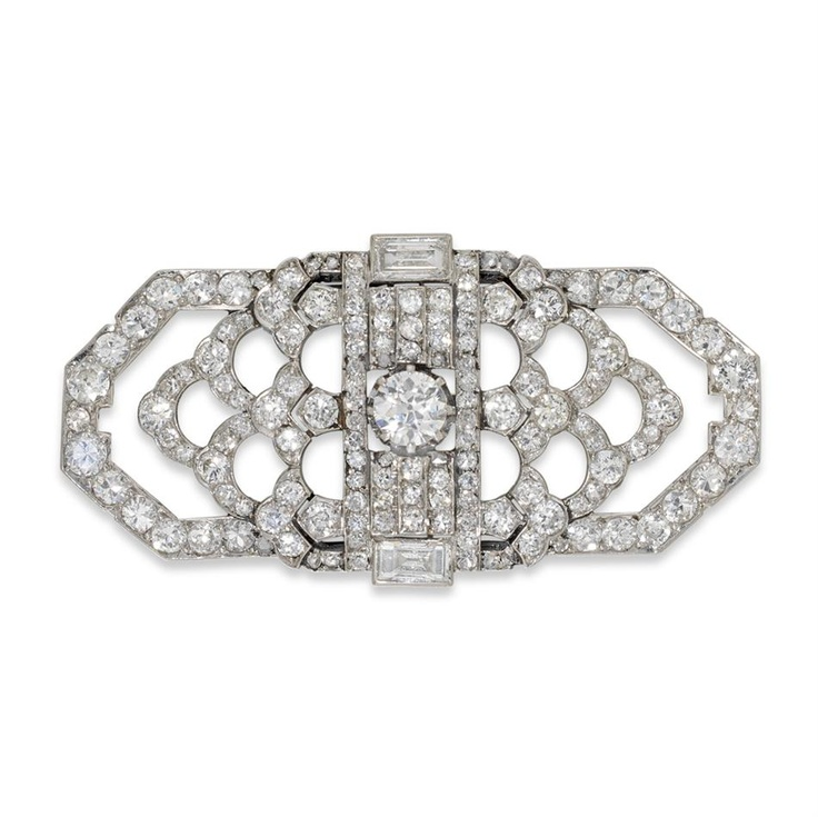 An Art Deco diamond set brooch, of rectangular shape with corners cut away, with an openwork pattern comprising of a central, round brilliant-cut diamond with an estimated weight of 0.35ct, with a baguette-cut diamond to the top and bottom of the rectangle, total estimated diamond weight 4.5cts,all mounted in white metal, tested and valued as platinum, overall dimensions 44x22mm, gross weight 11.4 grams, circa 1920.