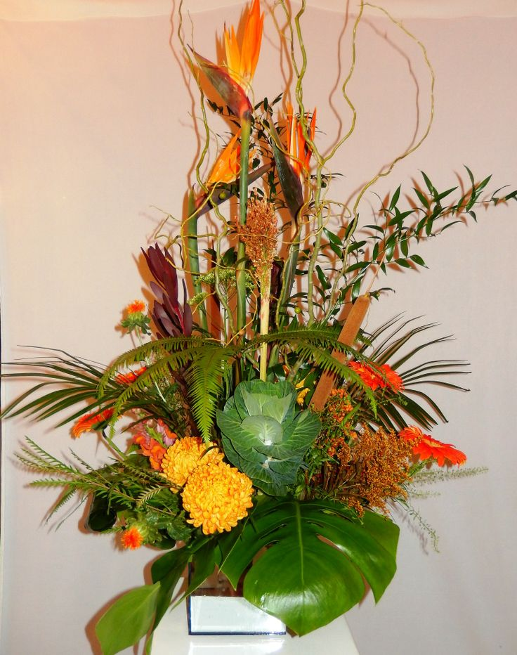 A stately lobby arrangement for a local company from Dizennio Floral Boutique in a modern mirror vase. Here lush tropical greens and Birds of Paradise are used to give volume and an exotic look
