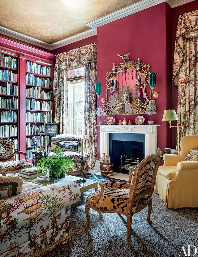 In the cherry-red library of this Mario Buatta–decorated South Carolina mansion, a chinoiserie fabric was used for curtains and upholstery | archdigest.com