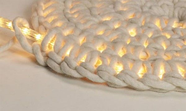 Crocheting around rope light to make an outdoor floor mat.