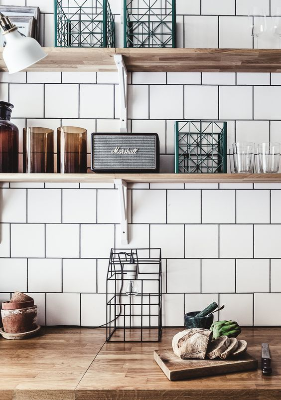Rustic wood counter and shelves with white tile and black grout.