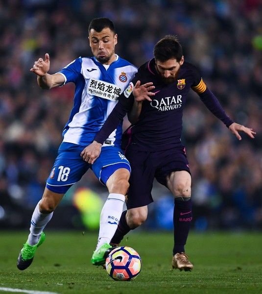 Lionel Messi of FC Barcelona competes for the ball with Javi Fuego of RCD Espanyol during the La Liga match between RCD Espanyol and FC Barcelona at the RCDE Stadium on April 29, 2017 in Barcelona, Catalonia.