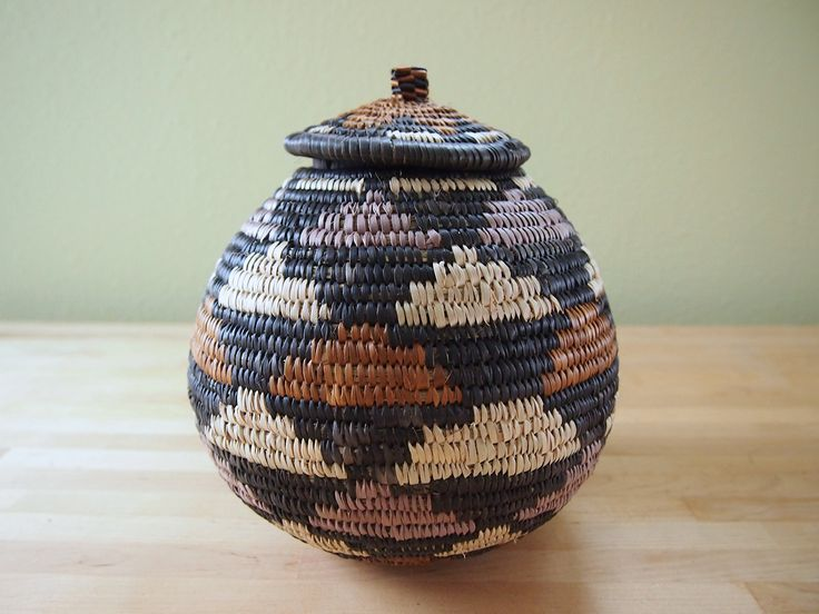 "African Zulu Beer Basket, Lidded Basket Woven in South Africa. This beer basket is a tightly woven, lidded basket crafted in South Africa and traditionally used to store the local brew. Each basket comes with a card explaining the patterning on the baskets and features the weaver's name. It's a beautiful art piece to add to your home. 7.5"" wide, 8.5"" tall."