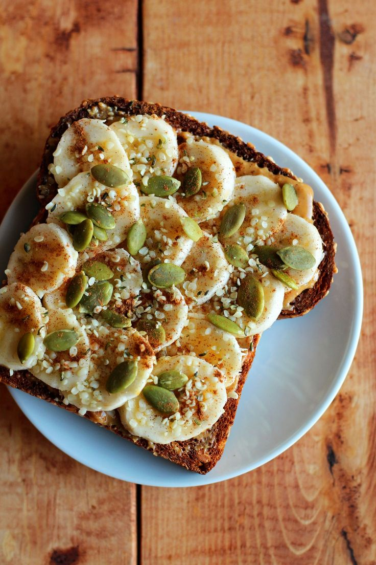Sliced banana and crunchy peanut butter on sprouted grain toast topped with pumpkin seeds, hemp seeds, cinnamon, and maple syrup.