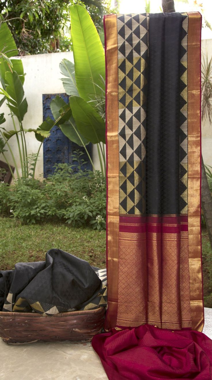 This kanchivaram silk is in ebony black with thread brocade work displaying a geometrical pattern all over. The saree has an interesting border with a ghicha work along the entire length, highlight…