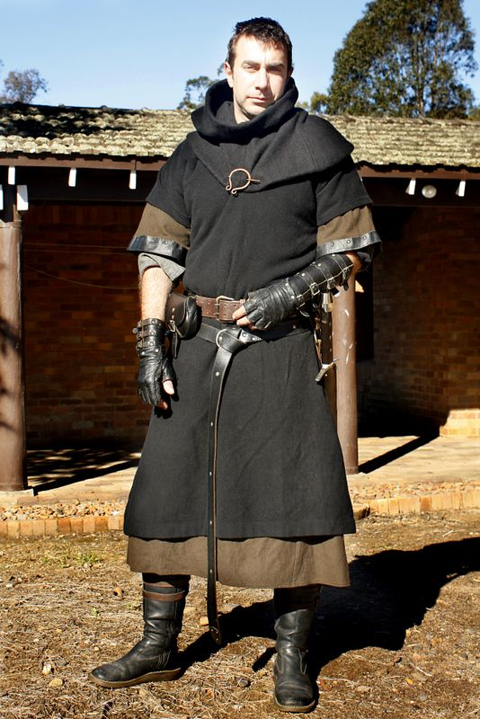 This costume is a fair bit more monkish than his previous ones, simply by matching the collar color with the outer tunic. The short sleeved gambeson underneath, exposing the seasoned bracers, is the only giveaway that this man knows more combat than his more immediate appearance belies.