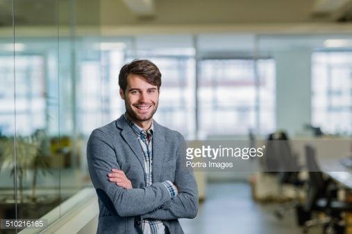 Photo : Happy businessman standing arms crossed in office #ManPortrait