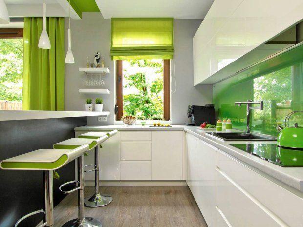 WYSTRÓJ WNĘTRZ - KOLORY. Zielony. Wystrój kuchni otwartej na pokój dzienny, z jednolitą białą zabudową, ożywiają dodatki w różnych odcieniach zieleni (konsekwentnie zastosowano je także w pokoju dziennym). W kuchni zieleń pojawia się nawet na suficie - na ten kolor pomalowano podłużną wnękę w podwieszonym suficie.