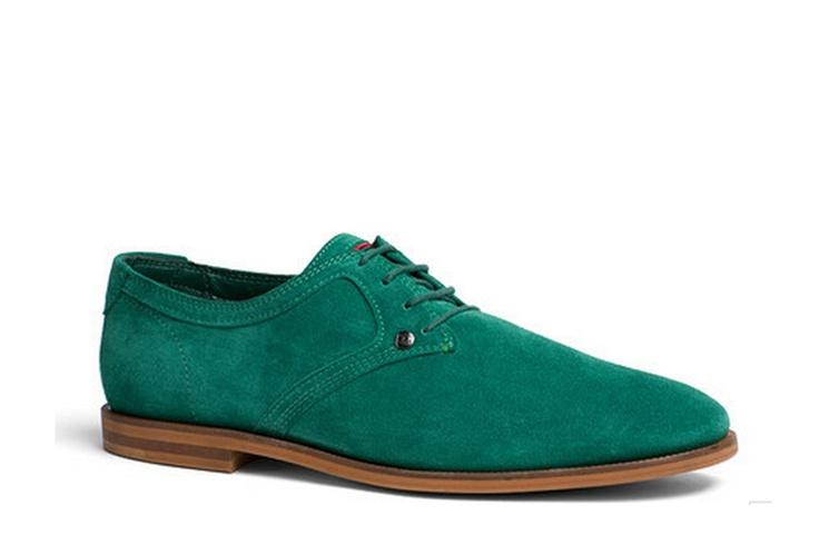 Zapato de ante verde modelo Adam 3B. Cierre con cordones en verde. Logo de la marca en el talón. Interior de cuero y piel. Suela de material sintético marrón de primera calidad. El zapato de vestir más cómodo y elegante de Tommy Hilfiger. Diseñado por Tommy Hilfiger.