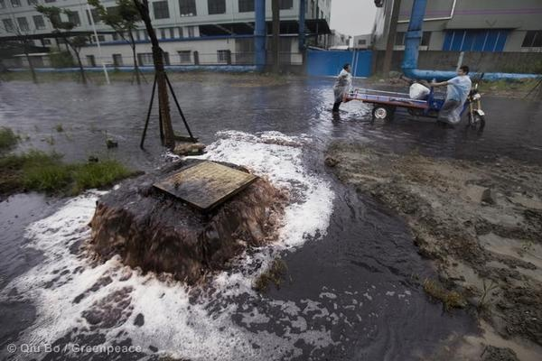 An underground pipe system of the water treatment plant is overwhelmed by the rainstorm and starts vomiting out waste water and flooding the streets.    Hangzhou Bay Economic Development Zone, Cixi City, Zhejiang: © Qiu Bo / Greenpeace