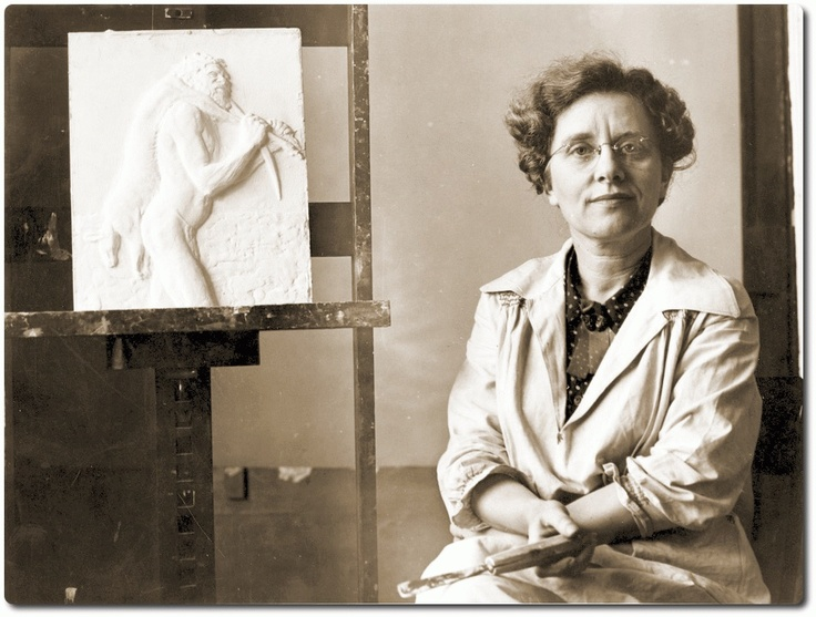 Daphne Mayo, 1941   Pictured with one of her bas relief casts, an Aboriginal design, for the bronze doors of the State Library of New South Wales, Sydney