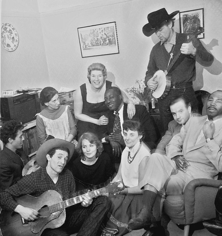 Big Bill Broonzy: Gathering at London apartment of Paul and Valerie Oliver, February–March, 1957, photographed by Paul Oliver. Top row, left to right: Alexis Korner (mandolin), Bobbie Korner, Beryl Bryden with arm around Bill, Derroll Adams (banjo). Bottom row, left to right: Ramblin' Jack Elliott (guitar), June Elliott, Valerie Oliver, Donald Kincaid (a friend of the Olivers), Brother John Sellers. Dave Bennett Collection.