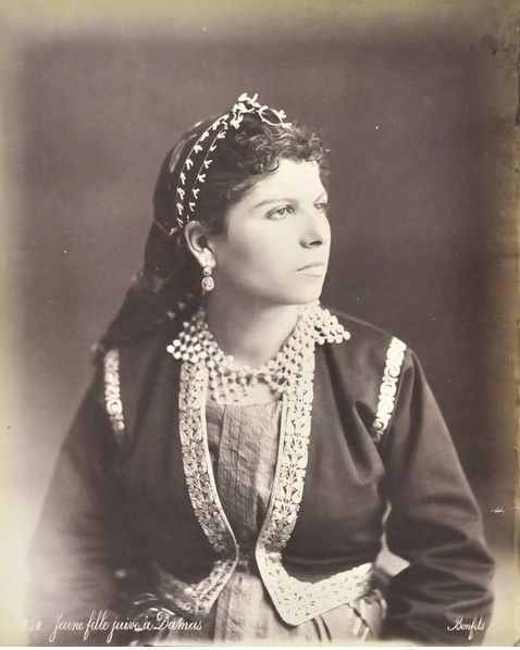 In the photograph, Bonfils captured a beautiful, affluent Syrian Jewish woman dressed in traditional finery. She wears a richly embroidered jacket over a dress, together with a headscarf over her hair. At her neck, a jewelled collar, in her ears cameo pendants. This picture provides a rare glimpse into that once vibrant community of Shami Jews.