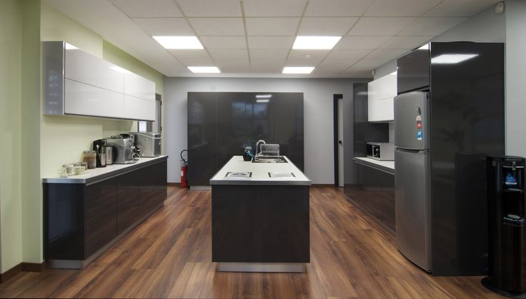 Kitchen with glossy, white and grey, lacquered cabinets and matte white countertop designed by AkPraxis for the new Offices of Loadline.