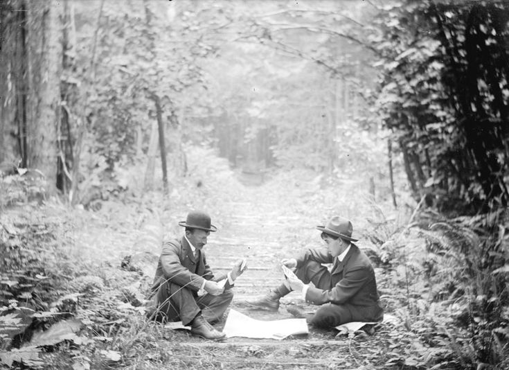 Two men playing cards in the middle of a logging road in Stanley Park, 1890's