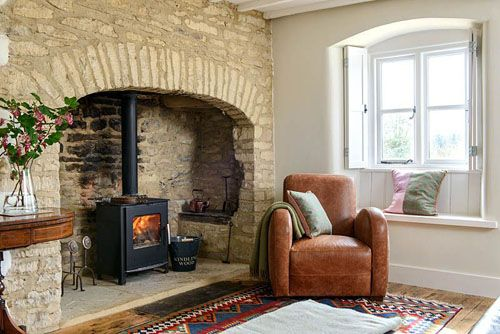 Leather armchair by fireplace - © Colin Poole/GAP Interiors