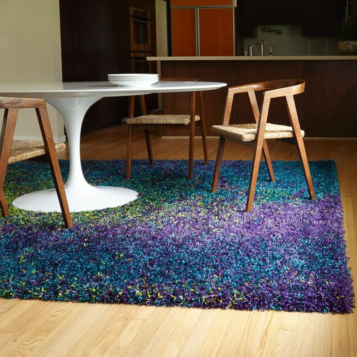 This beautiful contemporary peacock rug will add a modern look and a dazzling splash of color to your home or office with its bold hues and unique design. The vibrant purple and yellow details accentuate the teal background of this shag rug.