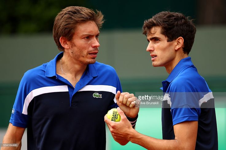 Nicolas Mahut (L) talks with Pierre-Hugues Herbert of France during the Men's Doubles first round match against Sam Groth and Bernard Tomic of Australia on day four of the 2016 French Open at Roland Garros on May 25, 2016 in Paris, France.
