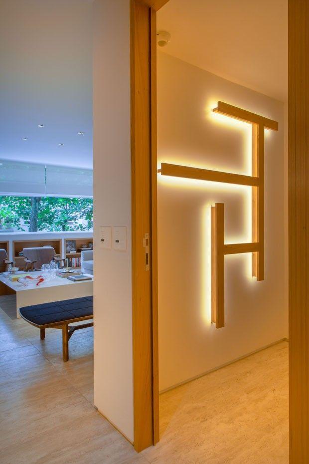 Corredor | A personalização dos ambientes é um dos destaques do apartamento, cheio de obras de arte e objetos pessoais. Outro acessório é o ornamento desenhado pela arquiteta. Com iluminação indireta, ele complementa o piso em madeira e garante um ambiente ainda mais aconchegante (Foto: André Nazareth/Divulgação)
