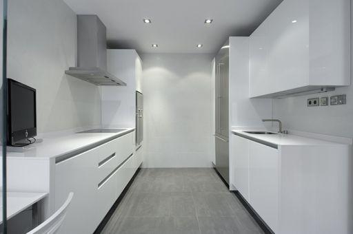 Suelo gris en la cocina y muebles blancos..