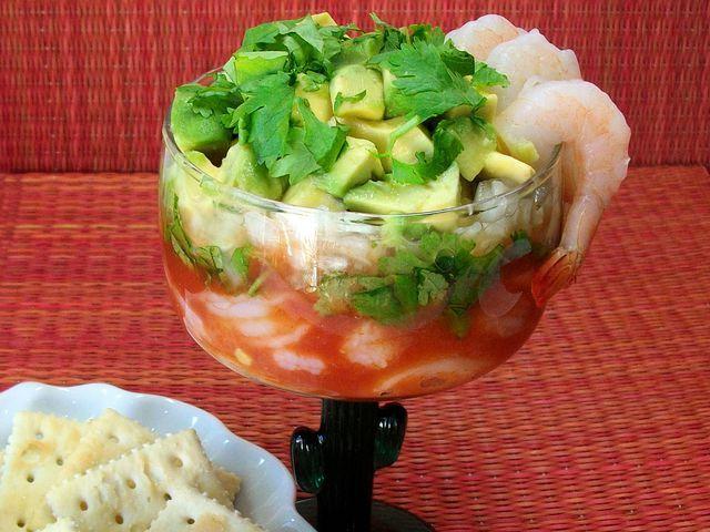 Trae la playa a tu paladar con esta deliciosa receta: cocktail de camarones con cebolla, cilantro, aguacate y refrescante salsa de tomate y naranja.