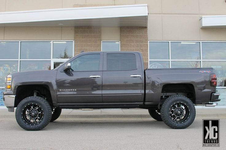 FUEL Offroad Krank 20x9.0 D517 black/milled wheels mounted with Toyo Open Country AT2 tires, AMP power side steps, Rough Country 7 inch suspension lift kit and KC Trends window/tail-light tint on a 2014 Chevrolet Silverado.