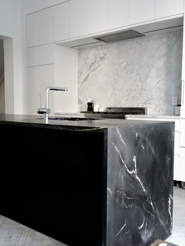 Take a look at how stunning this Black Moon Soapstone island, with a waterfall looks! It works perfectly with these white cabinets and Italian Marble.