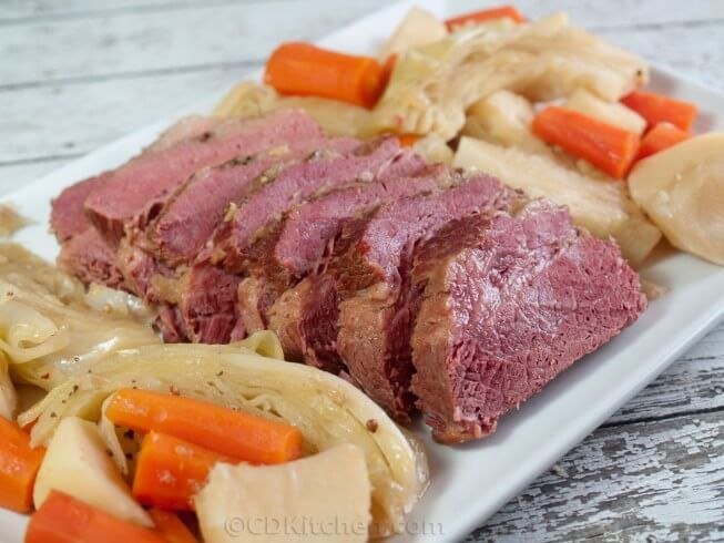 Flat cut corned beef brisket is simmered in Guinness with seasonings, potatoes, carrots, and cabbage wedges.