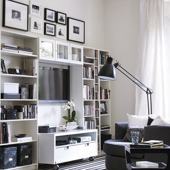 Modern living room storage. Use a combination of open shelves of differing sizes, cupboards and a media unit on wheels to store practical clutter and display accessories. Use wasted wall space above your unit to display photos.