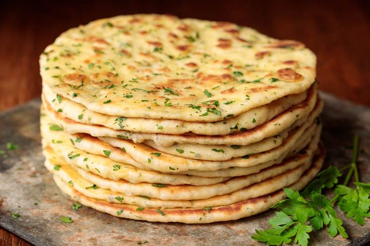 Photo of a stack of Greek Yogurt Turkish Flatbread (Bazlama) on a slate surface resting on a wood table.