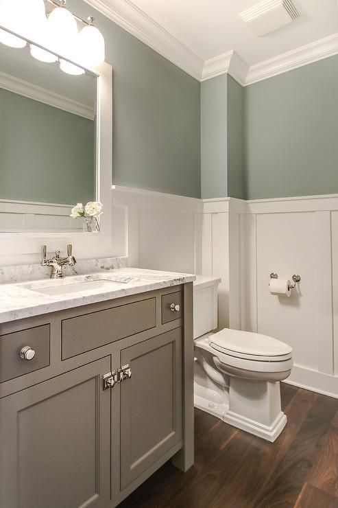 Tranquil bathroom features upper walls painted gray green and lower walls clad in board and batten lined with a creamy gray washstand topped with white marble under a white Parsons mirror illuminated by a three light downlight sconce.