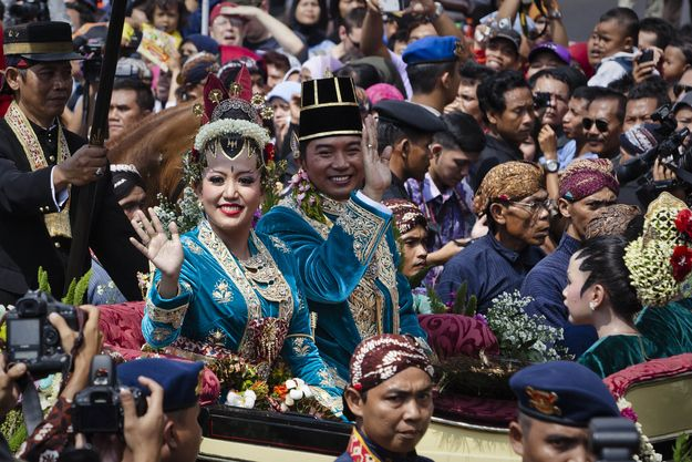 Huge crowds line the streets of Yogyakarta as bride Gusti Kanjeng Ratu Hayu and groom KPH Notonegoro are driven to Kraton Palace for their wedding. | 27 Beautiful Photos From The Royal Wedding In Indonesia