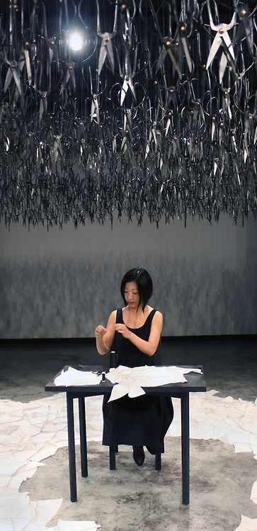 "Beili Liu - The Mending Project (2011)    ""The piece involved the artist sitting at a small black table, hand-mending patches of fabric together which visitors were encouraged to cut themselves near the entrance....The hovering mass of the downward-pointed scissors represent the distant fear and looming violence present in today's cultural climate. The sharp blades above the artist are put in contrast by the silent and simple act of mending."""