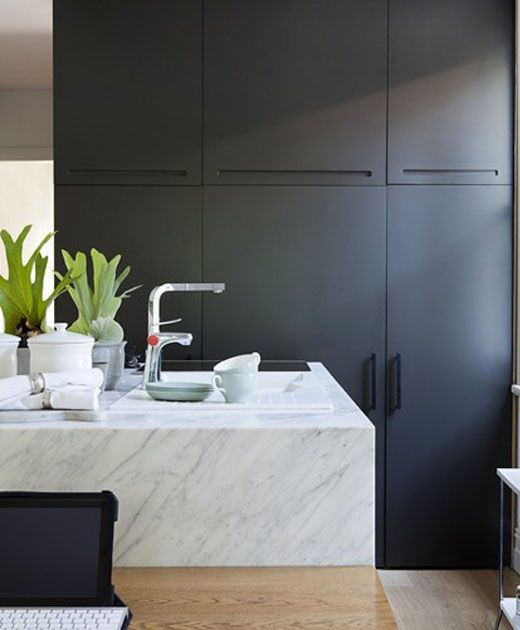 black cabinetry. white marble island