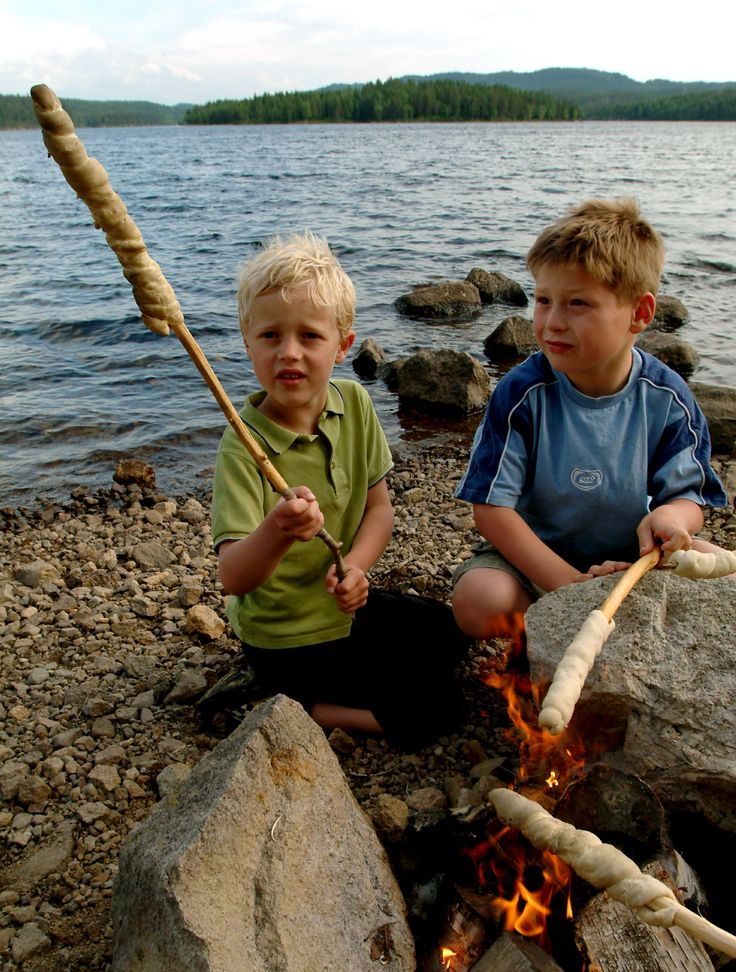 Children grilling 'bread on a stick' on the campfire. All