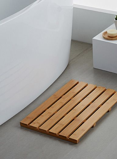 Exclusivité Simons Maison Une descente de bain très épurée en lattes de bambou pour une ambiance spa scandinave dans la salle de bains Pattes de caoutchouc permettant un contact au sol coussiné Construction durable, fait à la main Format rectangulaire, 36x54 cm