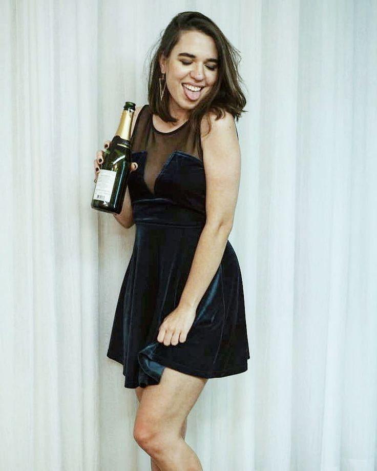 Look de festa para o ano novo com champagne. Vestido curto de veludo verde com transparência. Morena de cabelo curto. Look do dia para blog de moda.