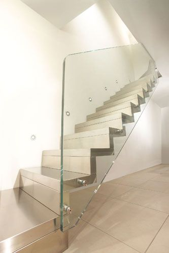 Closed cantilever staircase with stainless steel steps and risers,    with ultra-clear Structured glass banister