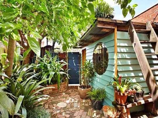 Cutest and coolest tropical garden. The whole look of the garden and the house is eclectic perfection.