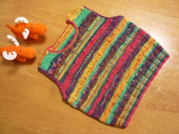 赤、緑、黄 カラフルな段染糸で編んだ、かわいいベストです。男の子、女の子、どちらのお子様にも着て頂けます。棒針編みで脇下までは表編みと裏編の組み合わせで、ヨー...|ハンドメイド、手作り、手仕事品の通販・販売・購入ならCreema。