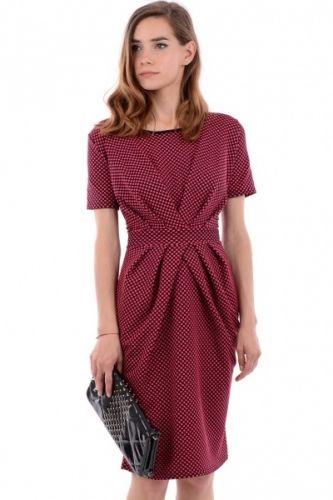 Mørkt rosa farget kjole med sorte prikker og sort krage i halsen. Kjolen rekker ned til knærne og har korte armer. Den er også snurpet sammen i livet med ett innsydd belteparti som gir kjolen ett klassisk utseende.