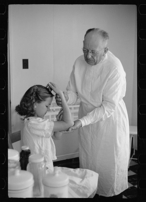 Doctor examining a little girl's broken arm in 1942 - photo taken by Arthur Rothstein