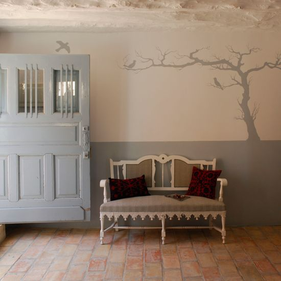 Hallway with square brick flooring, rugged grey door and upholstered bench