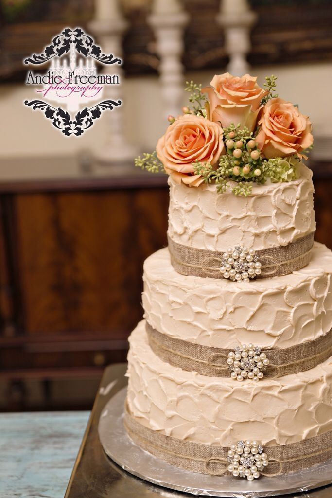 Three tiered rustic wedding cake wrapped in burlap with pearl broaches and flower topper. Country fall wedding. Photography: www.TheAthensWeddingPhotographer.com Coordinating: Wild Flower Event Services Venue: The Thompson House and Gardens Floral: Flowers by On #floralweddingcakes #fallweddingflowers