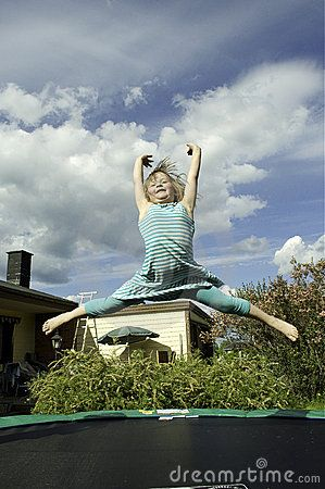 A young girl jumping on a trampoline.