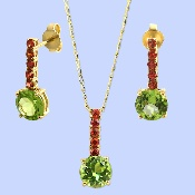 Eye-catching, sensual and beautiful, jewelery set: necklace-pendant with matching earrings. Center stone- Soft Green Peridot accented with rare Orange Sapphires. The glamorous design is crafted of glittering 18K yellow gold.CONTACT US FOR MORE INFORMATION! T: 5148452900 OR info@eskimofire.com
